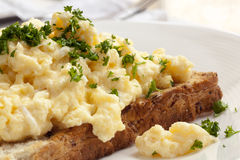 Scrambled Eggs on Toast. Ed wholegrain bread.  Garnished with parsley Royalty Free Stock Photos