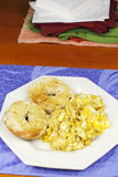Scrambled Eggs and a Toasted Bagel Breakfast. Two halves of a toasted, buttered everything bagel on a plate with scrambled eggs. Mustard with scrambled eggs and royalty free stock photo