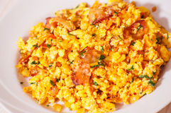 Scrambled eggs with tomato and bacon Stock Photo
