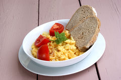 Scrambled eggs with tomato and bread Stock Image