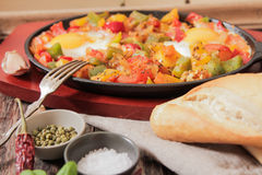 Scrambled eggs with tomato and peppers traditional breakfast. Scrambled eggs with tomato pepper traditional breakfast bread and salt royalty free stock image