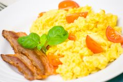 Scrambled eggs with tomatoes and bacon Royalty Free Stock Image