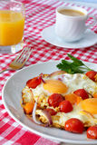 Scrambled eggs with tomatoes, coffee and orange juice. Traditional breakfast.Scrambled eggs with tomatoes on a white plate. cup of coffee and a glass of orange Royalty Free Stock Photos