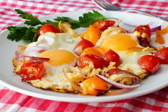 Scrambled eggs with tomatoes. Traditional breakfast.Scrambled eggs with tomatoes on a white plate.Checkered tablecloth Royalty Free Stock Photography