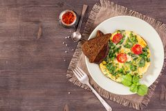 Scrambled eggs top view. Scrambled eggs with kale and toast on wooden table. Top view with copy space Royalty Free Stock Photos