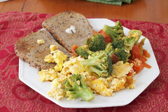 Scrambled Eggs Vegetables and Toast Breakfast. Octagon plate with breakfast food of scrambled eggs cooked with broccoli and tomatoes with buttered toast. Big Stock Image