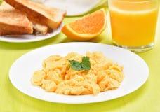 Scrambled eggs on white plate, toast and orange juice Royalty Free Stock Photos