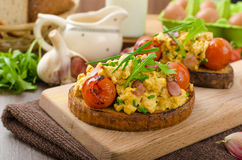 Scrambled eggs witch bacon, herbs and tomato Stock Photography