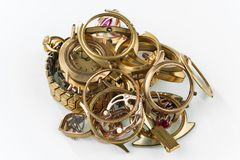 A scrap of gold. Old and broken jewelry, watches of gold and gold-plated on a white background. A scrap of gold. Old and broken jewellery, watches of gold and royalty free stock image