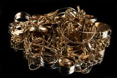 A scrap of gold. Old and broken jewelry on a black background stock images