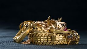 A scrap of gold. Old and broken jewelry. A scrap of gold. Old and broken jewellery, watches of gold and gold-plated on a dark background Royalty Free Stock Images