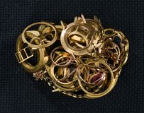 A scrap of gold. Old and broken jewellery, watches of gold and gold-plated against a background of a dark texture. A scrap of gold. Old and broken jewelry stock image
