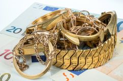 Old and broken jewelry, watches of gold and gold plated on a background of Euro banknotes. A scrap of gold. Old and broken jewelry, watches of gold and gold Royalty Free Stock Photos