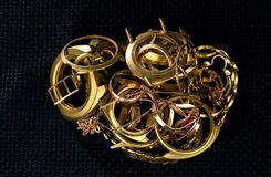 A scrap of gold. Old and broken jewelry, watches of gold and gold-plated on a dark background.  royalty free stock images