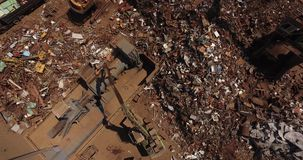 Scrap heap. Metal loaded into wagons by crane, view from above, cover shot stock video footage