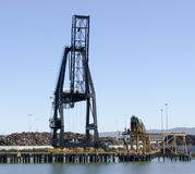 Scrap Metal Crane at Port. Large terminal cranes to load and unload scrap metal off and on ships for global commerce Stock Images