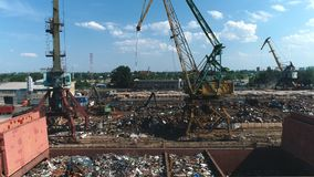Scrap metal, crane and train in port stock video footage