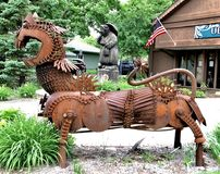 "Scrap Metal Dragon. This is a Summer picture of a piece of public art of a dragon on display along the ""Trollway"" located in Mount Horeb, Wisconsin stock photos"