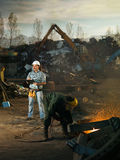 Scrap metal recycling center. Caucasian engineer standing at scrap metal recycling site, inspecting work Royalty Free Stock Images