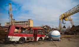 Scrap metal. Red broken bus and gas barrel. stock photography