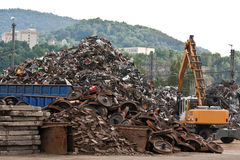 Scrap metal yard. Large pile of iron in scrap metal yard with heavy lifting machine in foreground royalty free stock photo