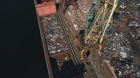 Scrap metal yard and crane on seaport, recycling materials stock footage