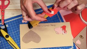 Scrap Valentine greeting card. Hands of girl making scrap Valentine greeting card stock footage