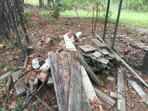Scrap Wood Pile. Some old boards from various projects. Some pieces of 2 x 4`s, some scraps from posts. Old metal and pine cones also in the mix. Weeds & leaves royalty free stock photos