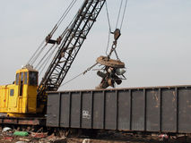 Scrap yard crane with magnet. Crane with magnet loading train car Stock Photography