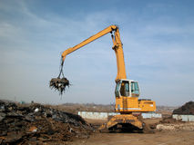 Scrap yard magnet. Crane with magnet in junk yard Stock Image