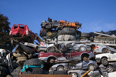 Scrap yard for obsolete motor cars. Scrap yard for obsolete motor cars with old wrecks and stripped vehicles piled high into the air on top of one another under Stock Photo