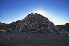 Scrap Yard Sorted Pile @ Sunrise. Sorted scrap metal piled high in a scrap yard under clear bright blue skies early in the morning stock image