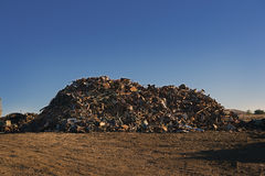 Scrap Yard Sorted Pile @ Sunrise. Sorted scrap metal piled high in a scrap yard under clear bright blue skies early in the morning royalty free stock photography