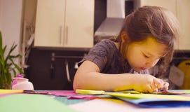 Scrapbooking Маленькая девочка клеит покрашенную бумагу стоковое фото rf