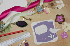 Scrapbooking. Hand made scrapbooking post card and tools lying on a table royalty free stock photos
