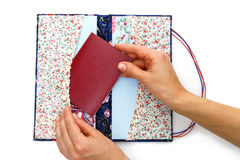 Scrapbooking holder for travel documents. Beautiful handmade scrapbooking holder for travel documents with ribbon closure. Floral fabric design. Femae hands Stock Images