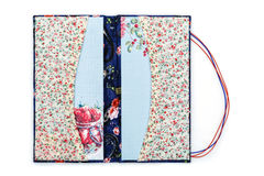 Scrapbooking holder for travel documents. Beautiful handmade scrapbooking holder for travel documents with ribbon closure. Floral fabric design. isolated on Royalty Free Stock Photography