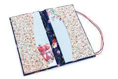 Scrapbooking holder for travel documents. Beautiful handmade scrapbooking holder for travel documents with ribbon closure. Floral fabric design. isolated on Royalty Free Stock Photos