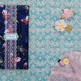 Scrapbooking holder for travel documents on floral paper. Beautiful handmade scrapbooking holder for travel documents with lace detail and ribbon closure lying Royalty Free Stock Photo