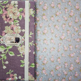 Scrapbooking holder for travel documents on floral paper. Beautiful handmade scrapbooking holder for travel documents with lace detail and ribbon closure lying Stock Images