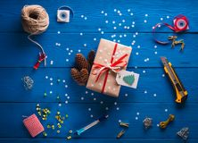Scrapbooking. Packing a Christmas gift in kraft paper on a blue wooden background. Scrapbooking. Packing a Christmas gift in kraft paper and a red ribbon on a Stock Image