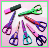 Scrapbooking Tools Of The Trade. Assorted crafting and scrap booking scissors and a pink highlighter on crafting paper Stock Photos