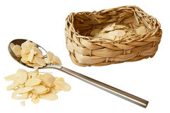 Scraped almonds with a basket and a spoon Stock Images