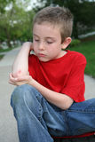 Scraped Arm. A young boy looks at his scraped elbow royalty free stock images