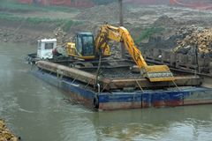 Scraper on a barge for the cleaning of the river bed of the Rive