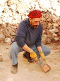 Scraping Bricks. A man scrapes excess cement from antique bricks being salvaged for further architectural use from the demolition site of an old Italian farm Royalty Free Stock Photography