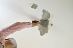 Scraping a Ceiling with a Tool Stock Photo