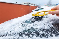 Scraping frozen snow from the car stock image
