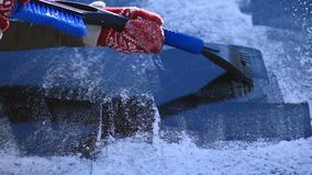 Scraping ice from car`s front windshield window stock footage