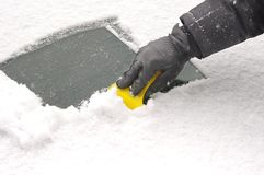 Scraping snow  from the car windscreen Stock Photo